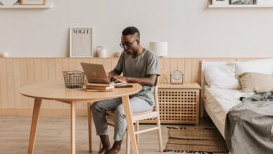 man-in-gray-crew-neck-t-shirt-and-blue-denim-jeans-sitting-on-white-couch-using-laptop